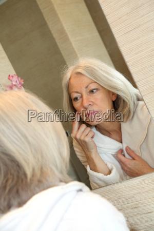 senior donna applicare crema idratante sul