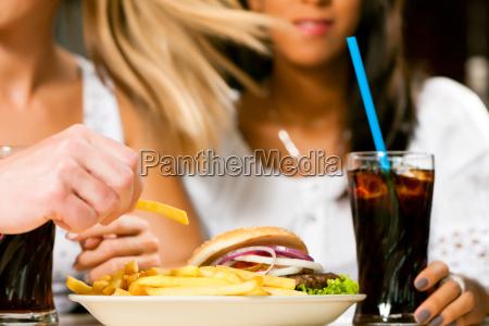 due donnemangiare hamburger e bere coca